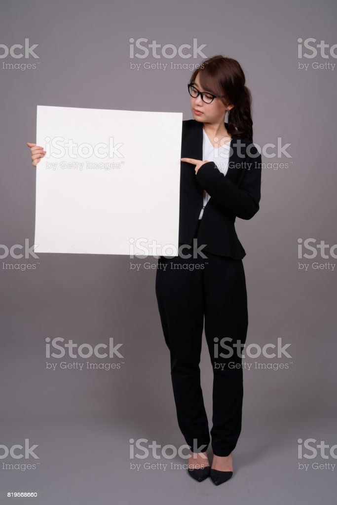 Studio shot of young beautiful Asian businesswoman holding placard against gray background stock photo