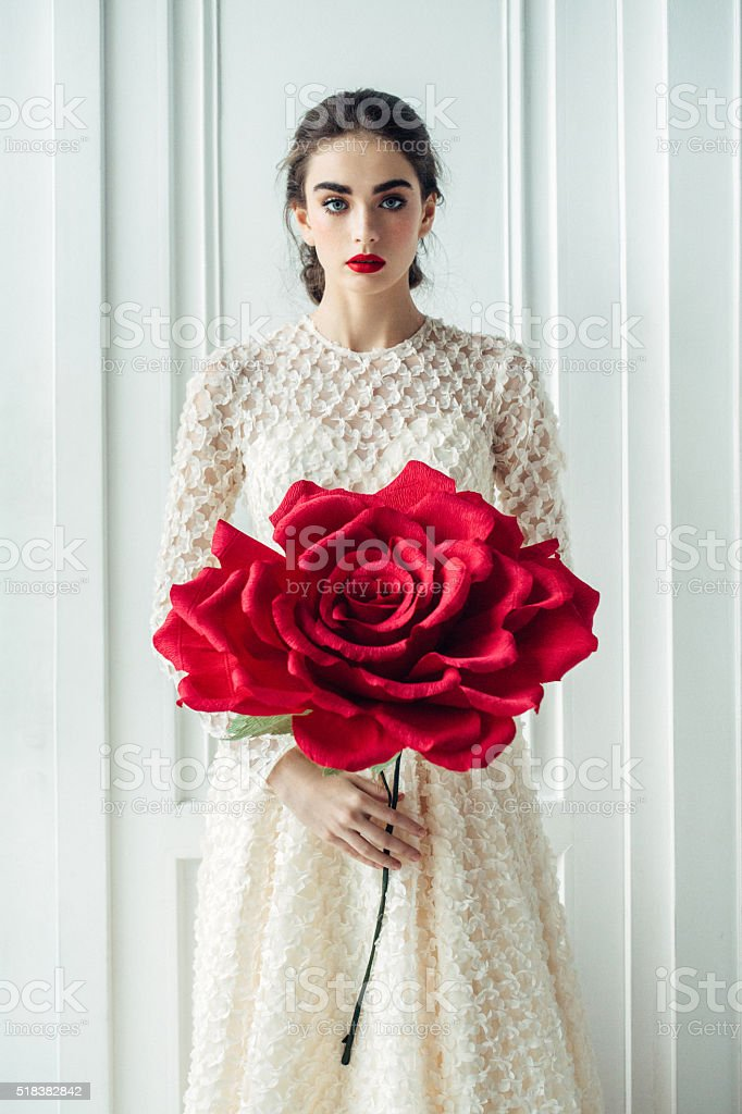 Studio shot of young beautiful bride with big rose stock photo