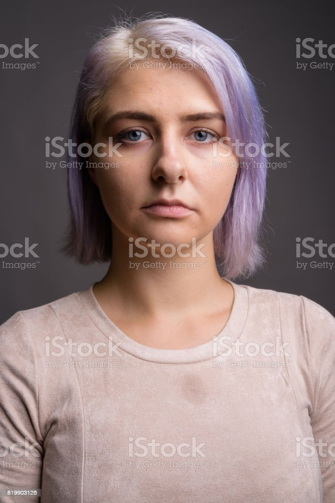 Studio shot of young beautiful rebel woman with colorful hair against...