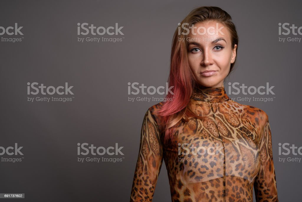 Studio shot of young beautiful woman against gray background stock photo