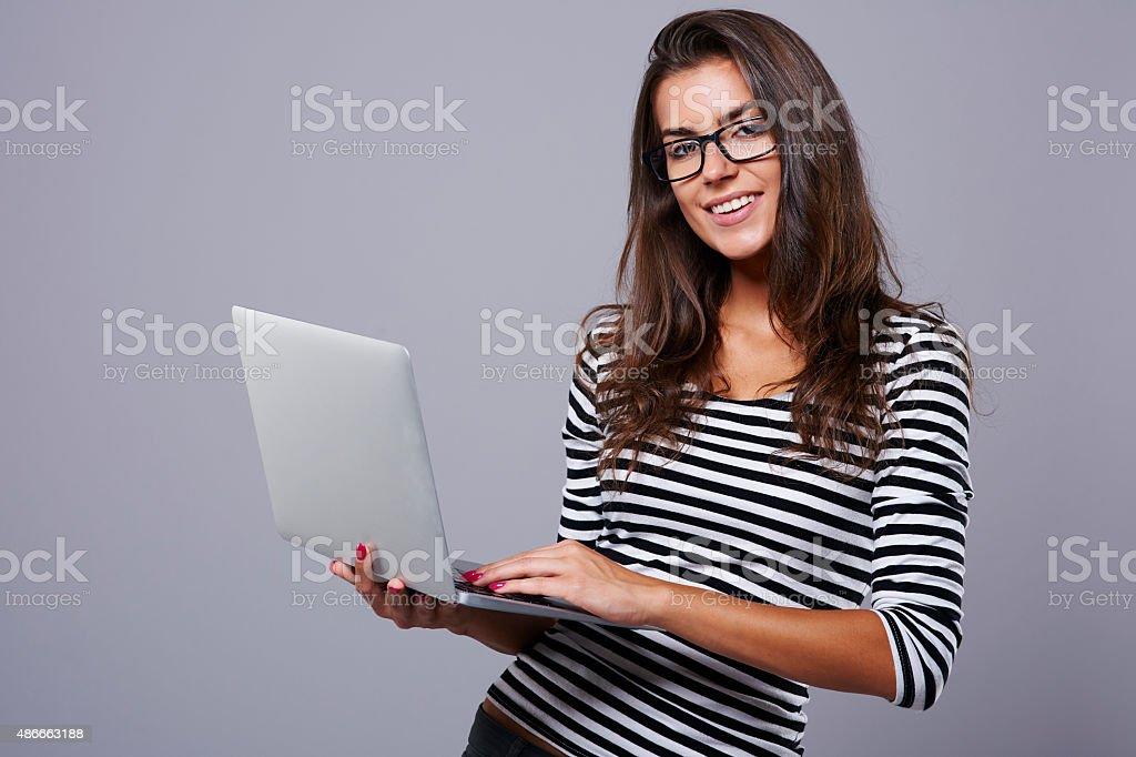 Studio shot of young brunette with laptop stock photo