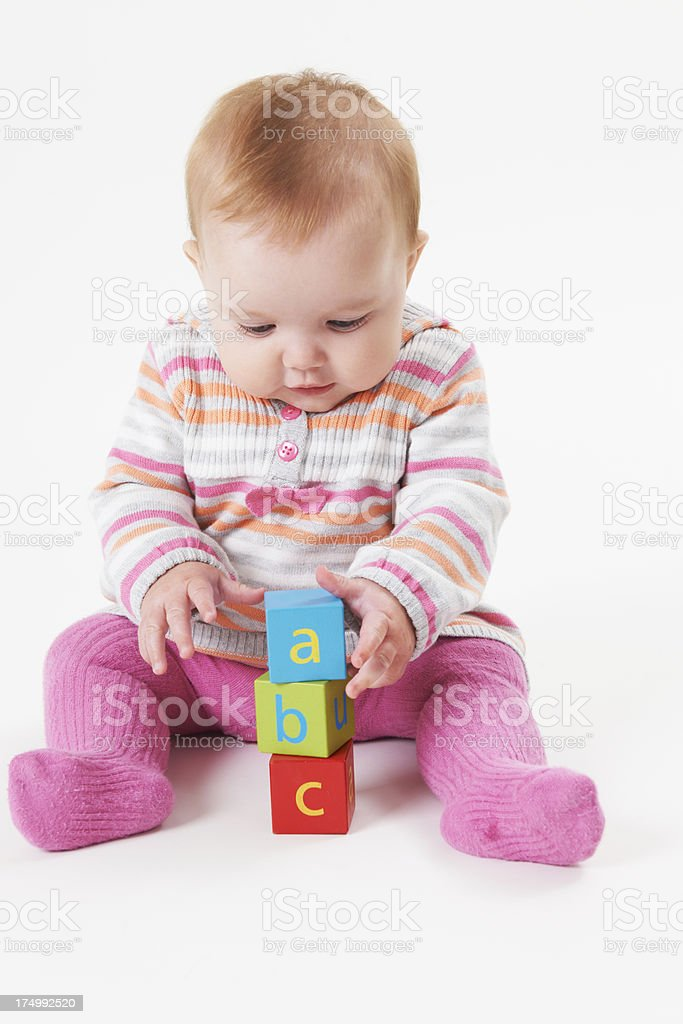 Studio Shot Of Young Girl Playing With Alphabet Blocks stock photo