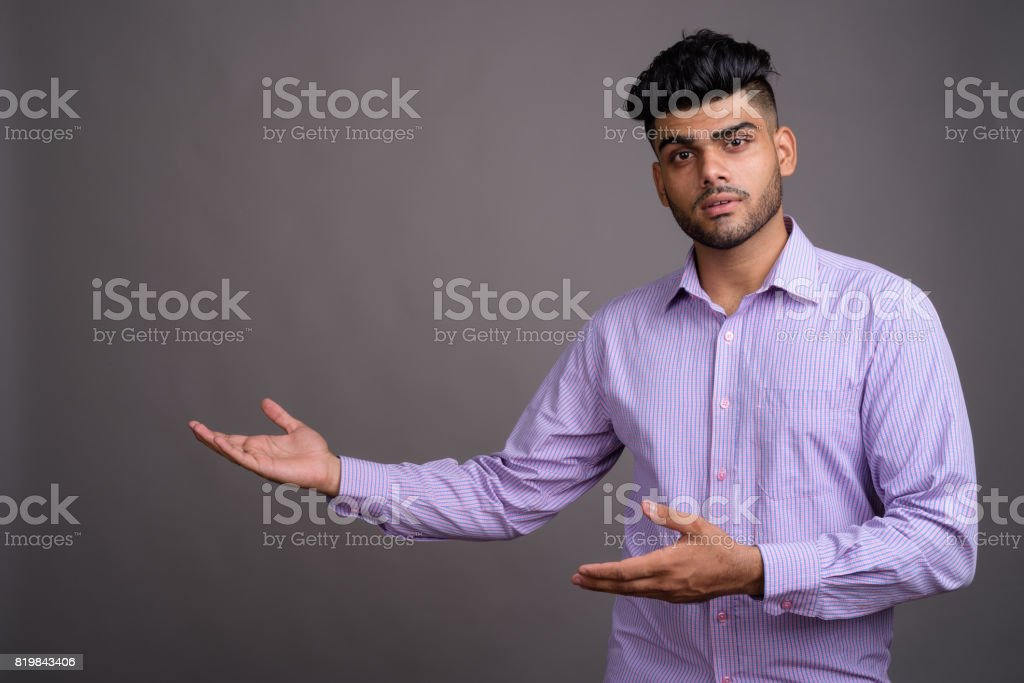 Studio shot of young handsome Indian businessman against gray background stock photo