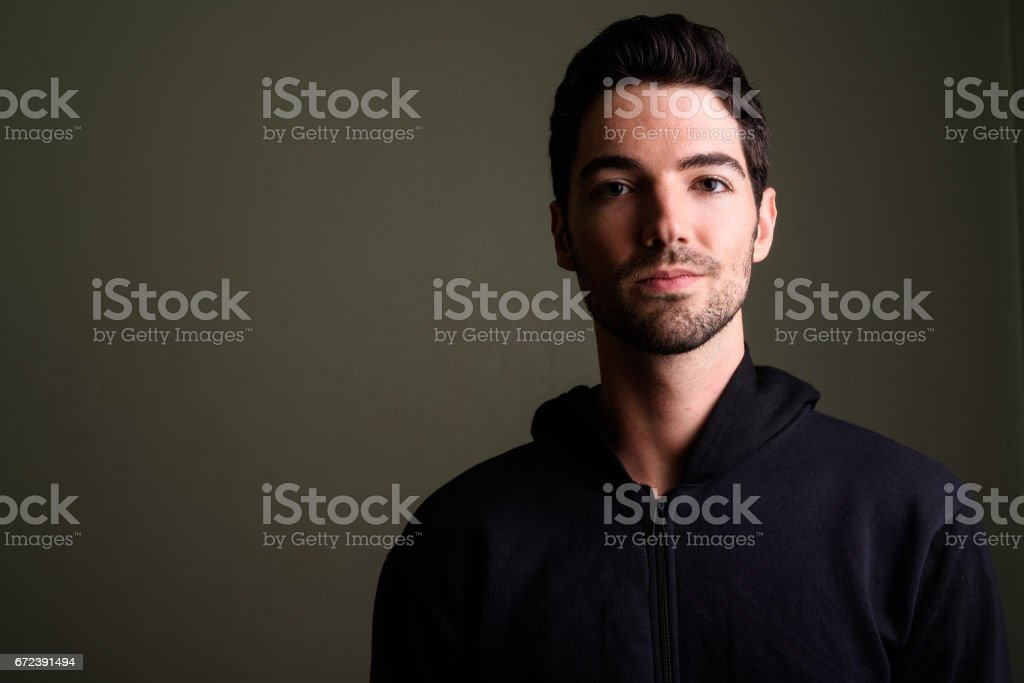 Studio shot of young handsome man against colored background stock photo