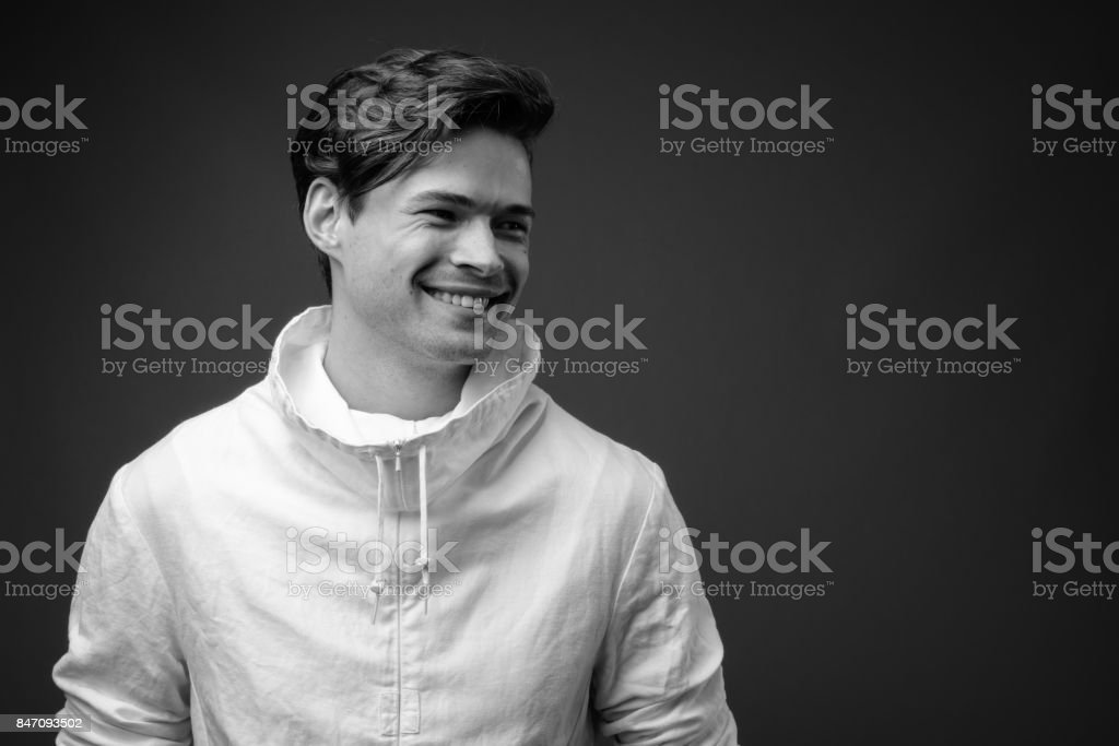 Studio shot of young handsome man wearing high collar white jacket against colored background stock photo