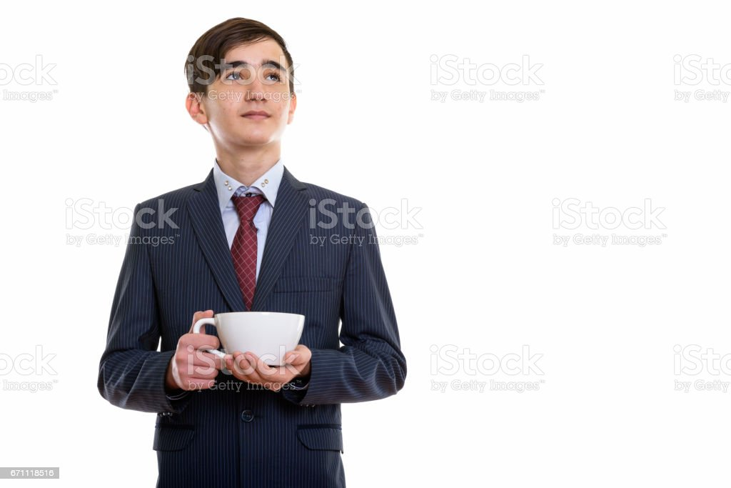 Studio shot of young handsome Persian teenage businessman holding coffee cup while thinking stock photo