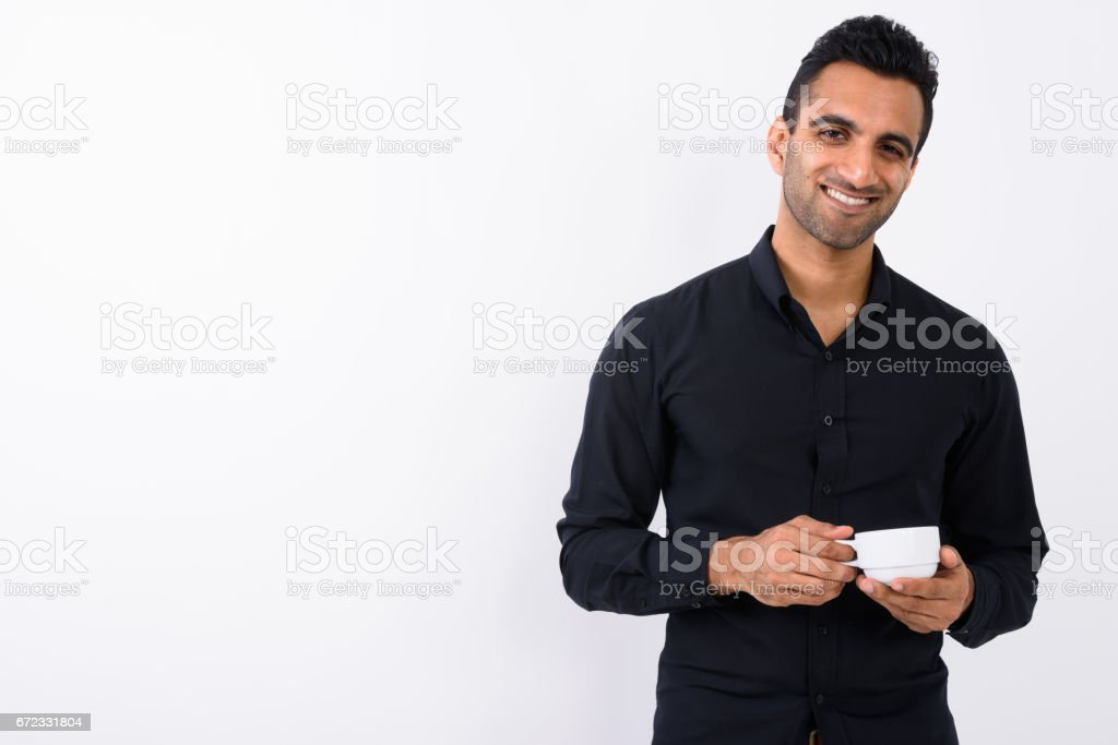 Studio shot of young happy Indian businessman smiling against white background stock photo