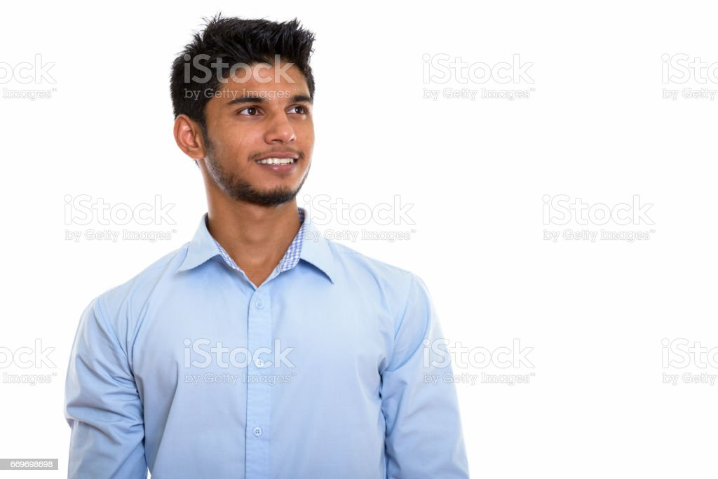 Studio shot of young happy Indian man smiling and thinking while looking up stock photo