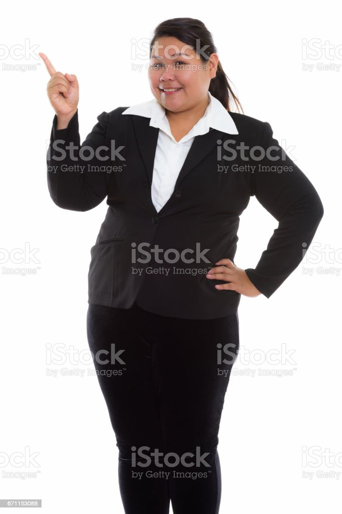 Studio shot of young happy fat Asian businesswoman smiling and standing while pointing finger up stock photo