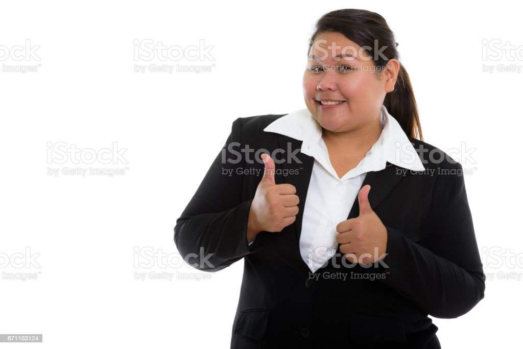 Studio shot of young happy fat Asian businesswoman smiling while giving thumbs up stock photo