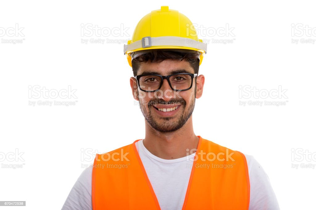 Studio shot of young happy Persian man construction worker smiling while wearing eyeglasses stock photo