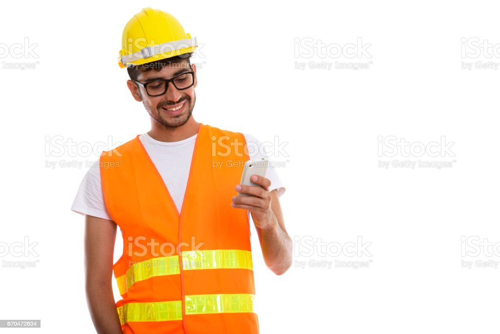 Studio shot of young happy Persian man construction worker smiling while using mobile phone stock photo
