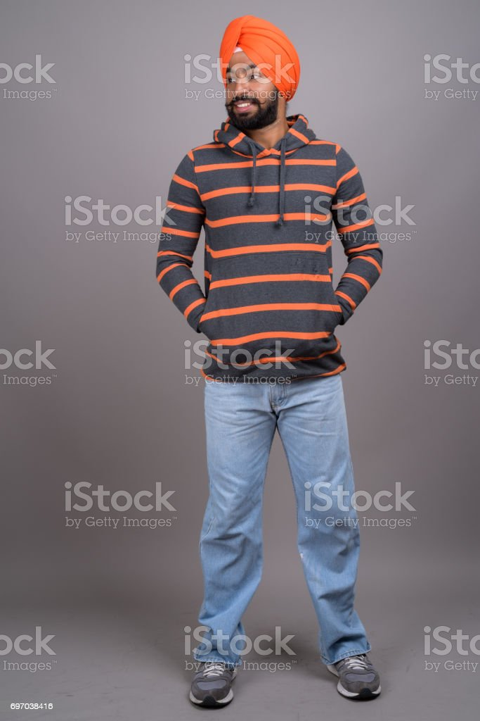 Studio shot of young Indian Sikh man wearing hoodie and orange turban against gray background stock photo