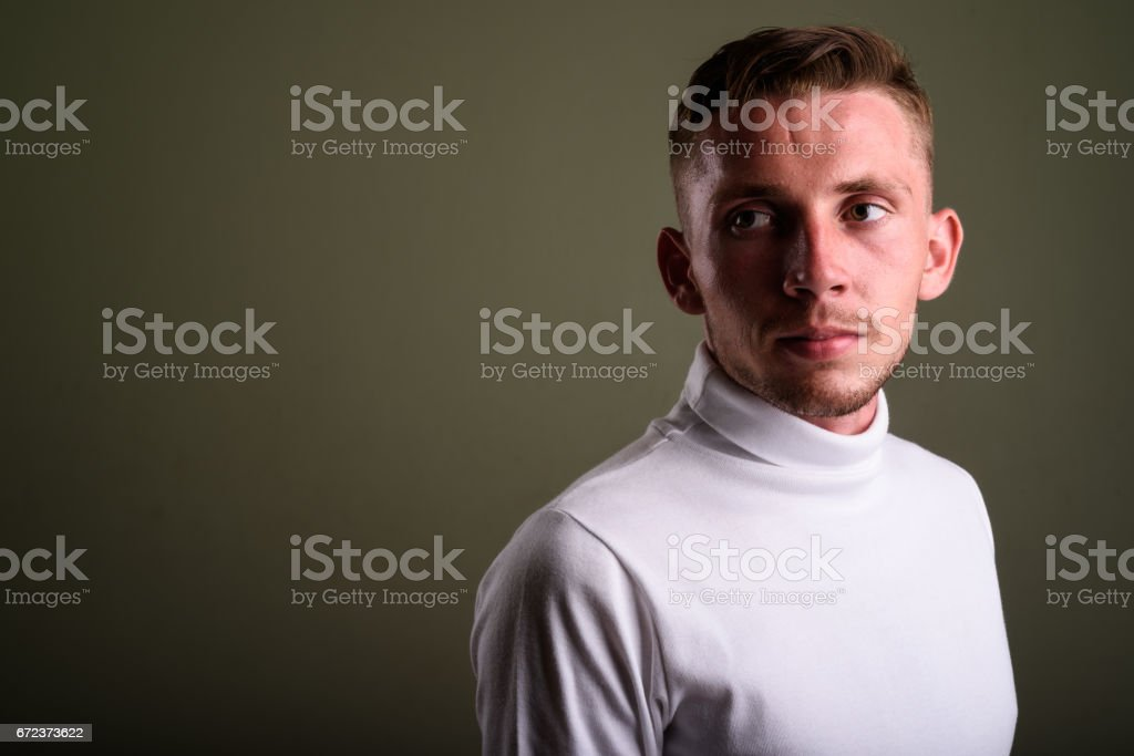 Studio shot of young man against colored background stock photo