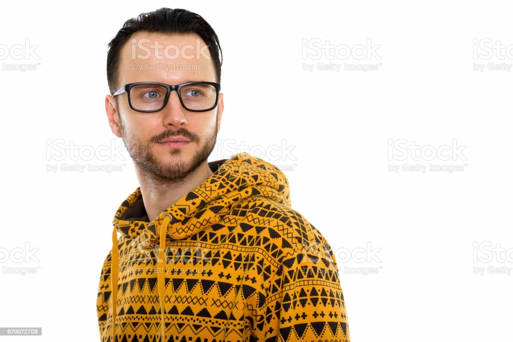 Studio shot of young man thinking while looking back and wearing eyeglasses stock photo