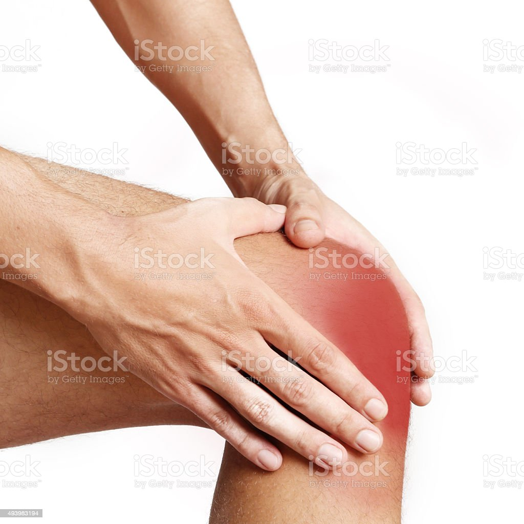 Studio shot of young man with knee pain stock photo
