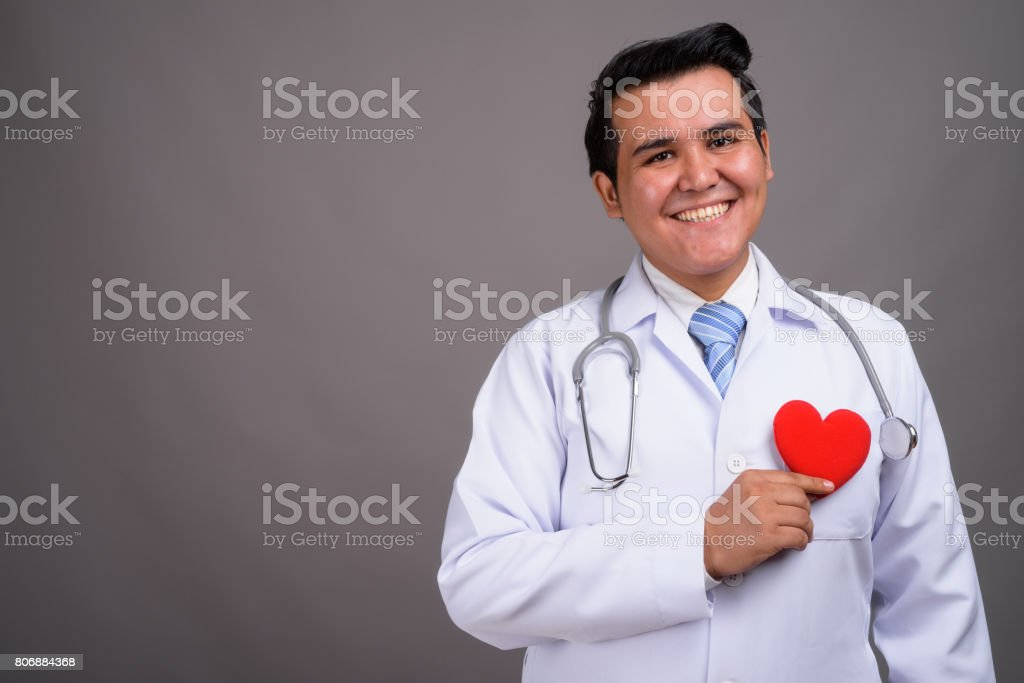 Studio shot of young multi-ethnic fat man doctor against gray background stock photo