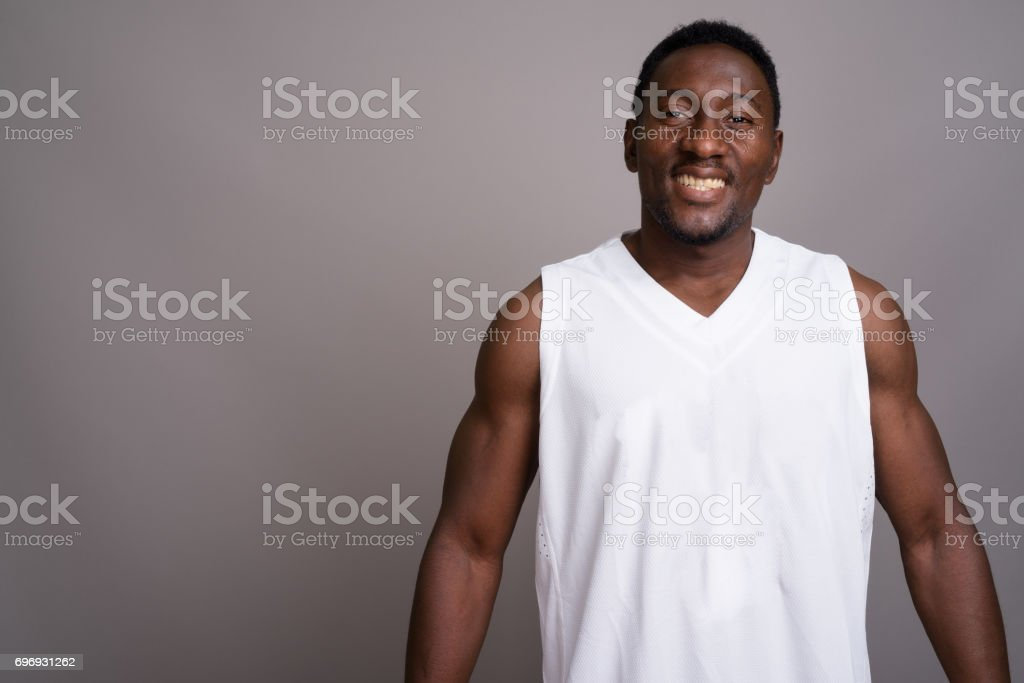 Studio shot of young muscular handsome African man against gray background stock photo