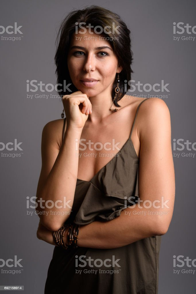 Studio shot of young woman wearing sleeveless dress against gray background stock photo