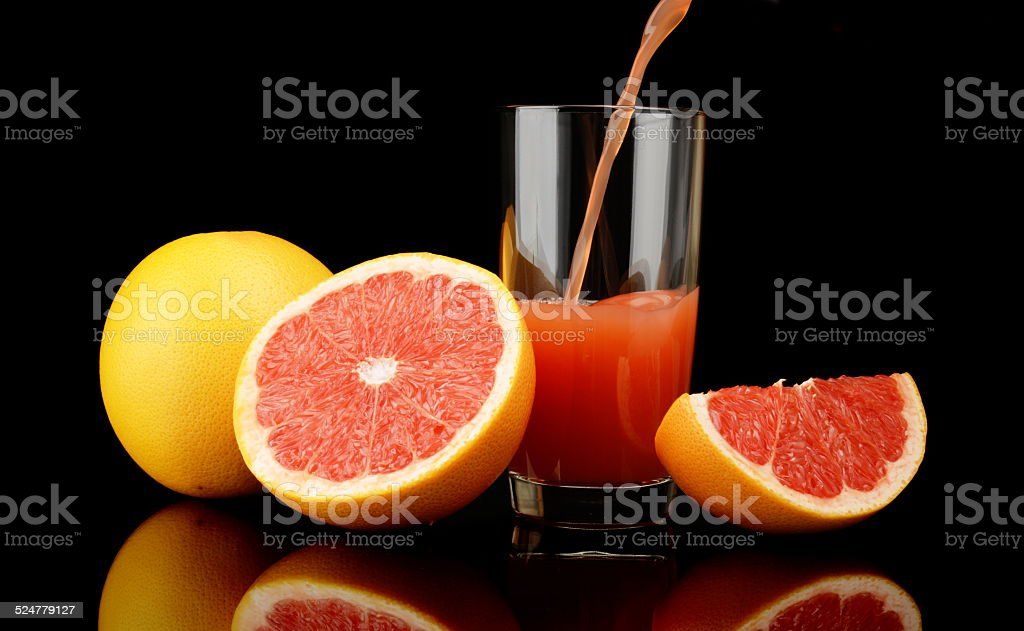 Studio shot sliced grapefruits with poured juice on black stock photo