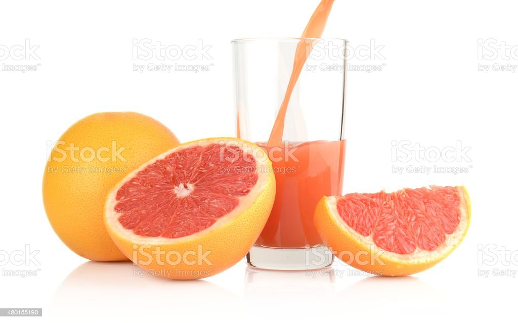 Studio shot sliced grapefruits with poured juice on white stock photo