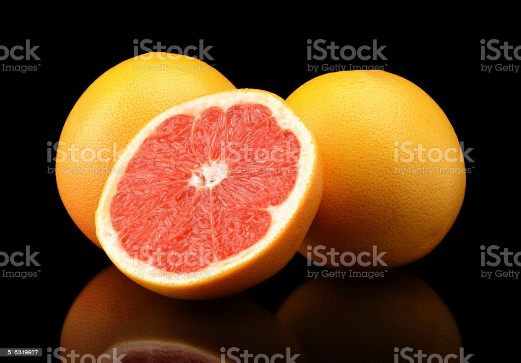 Studio shot sliced three grapefruits isolated black stock photo