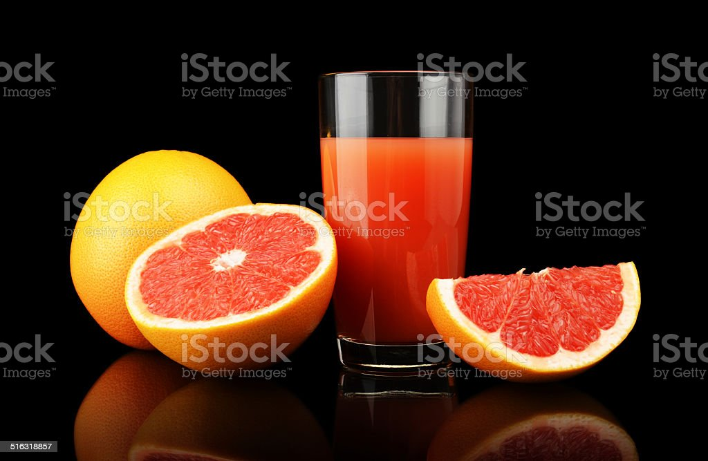 Studio shot sliced three grapefruits with juice isolated black stock photo