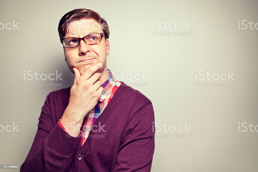 Studious young man ponders intently stock photo