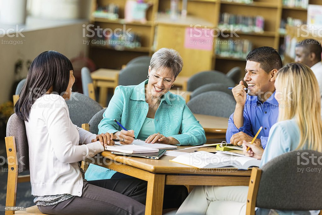 Study group of adult students at a wooden table stock photo