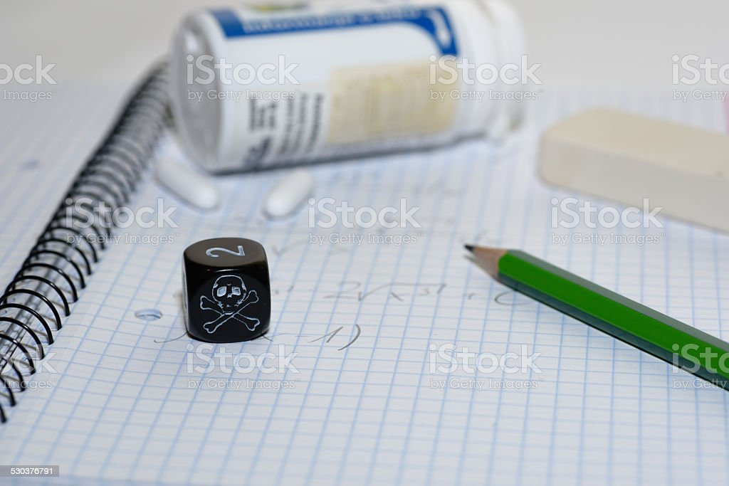 study place with painkillers in background and skull dice stock photo