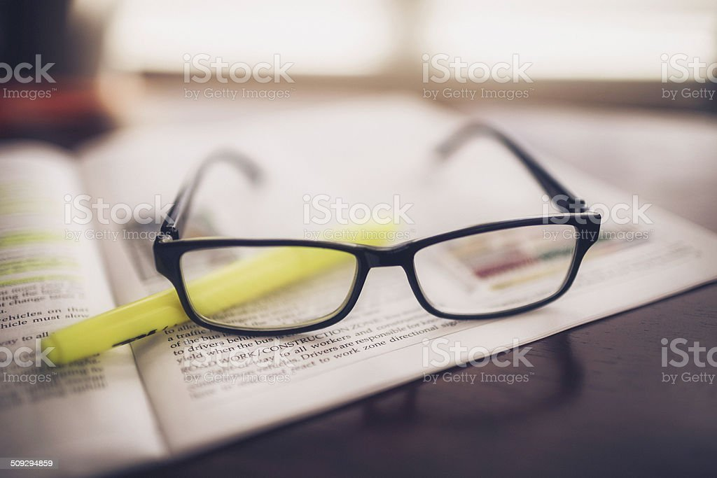 Studying for Driving Test: Handbook and Glasses stock photo
