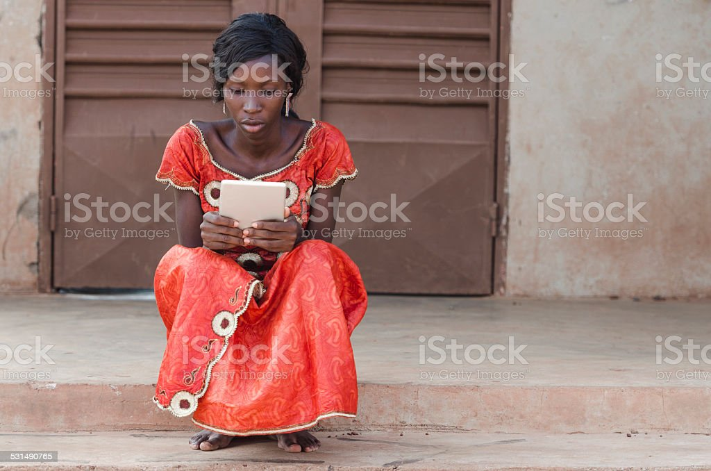 Studying Symbol: African Ethnicity Girl Reading Tablet Computer Laptop Mali stock photo