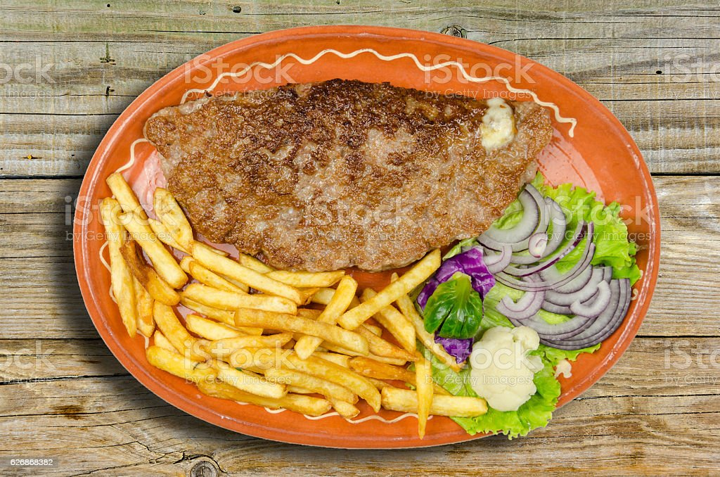 stuffed burger with salad and fries stock photo