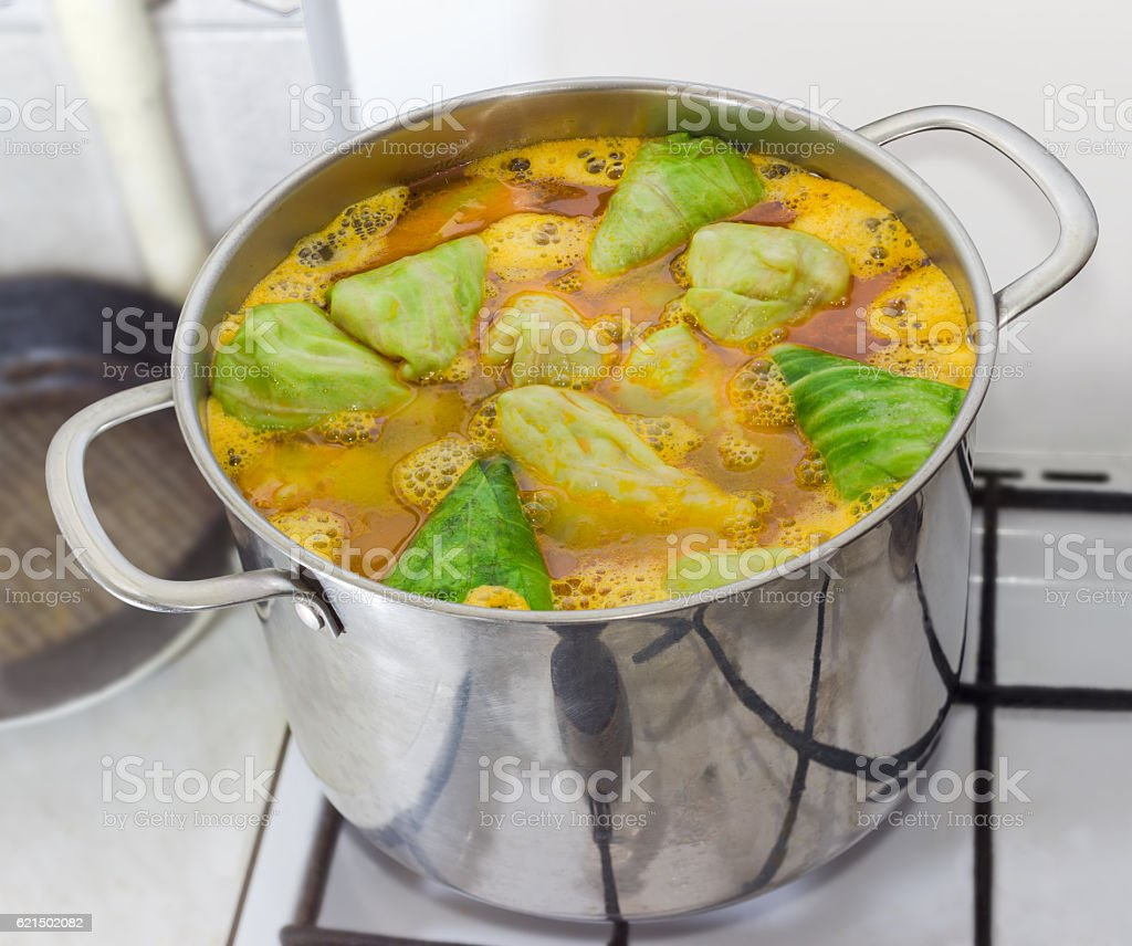 Stuffed cabbage rolls in boiling sauce during cooking stock photo