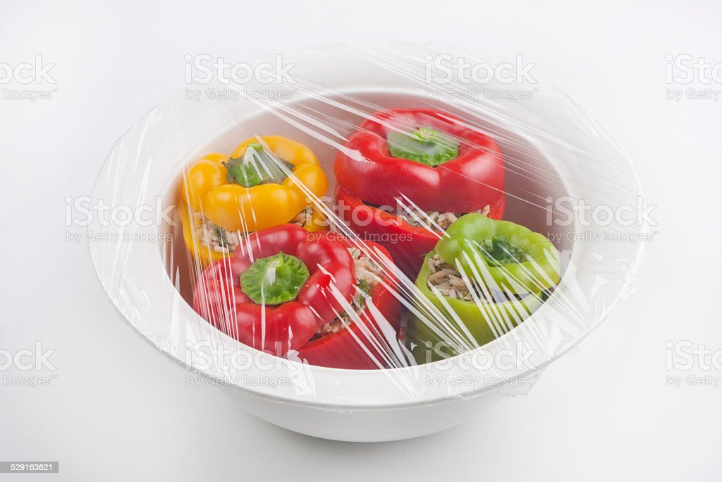 Stuffed peppers in cling film stock photo