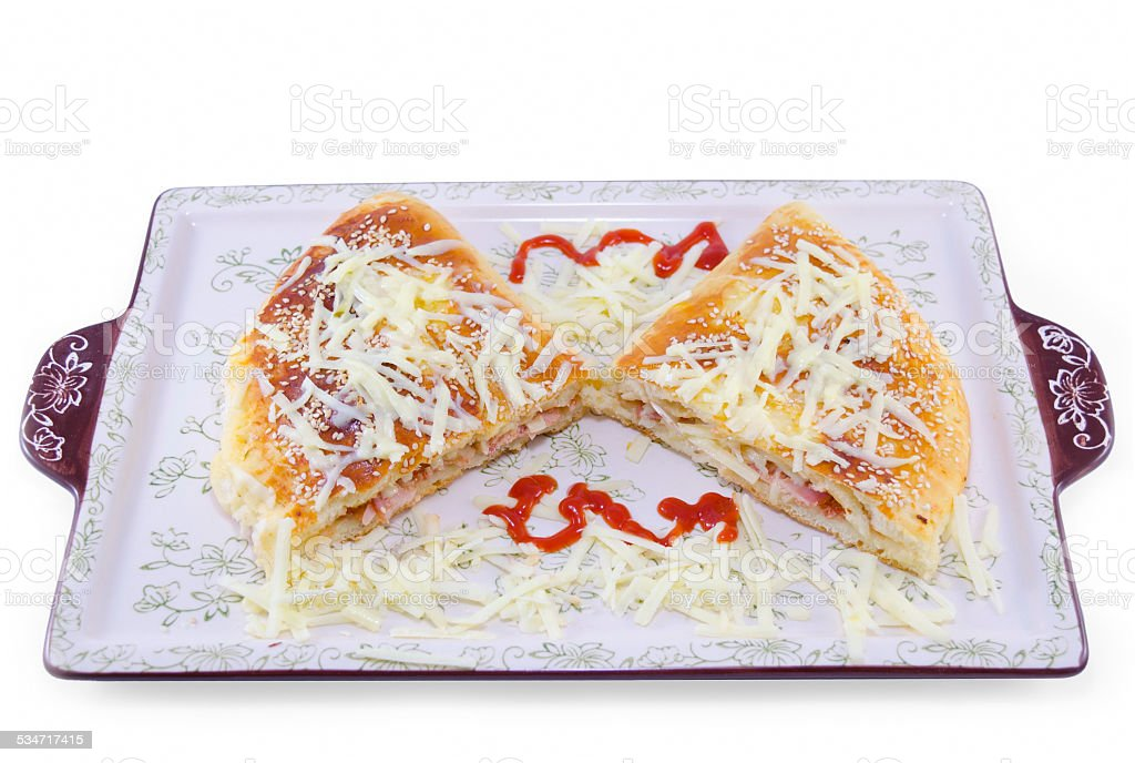 Stuffed pizza cut in half decorated with grated cheese royalty-free stock photo