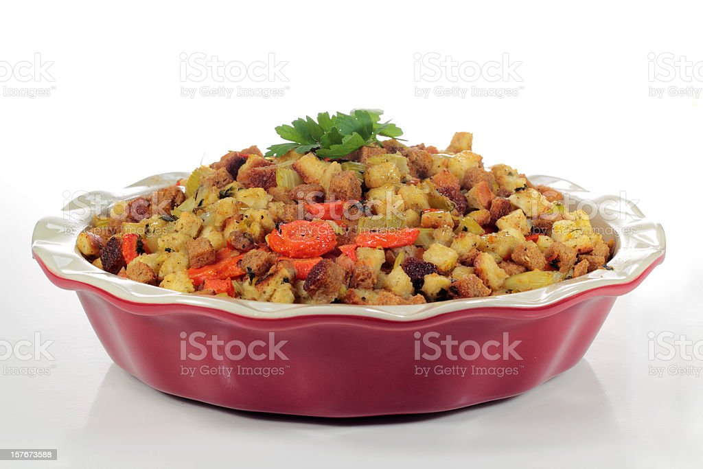 Stuffing being served in a red casserole dish stock photo