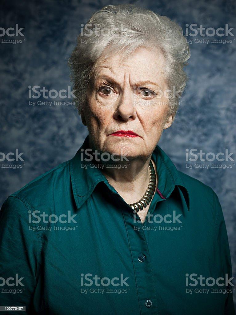 Stuido portrait of angry senior woman stock photo