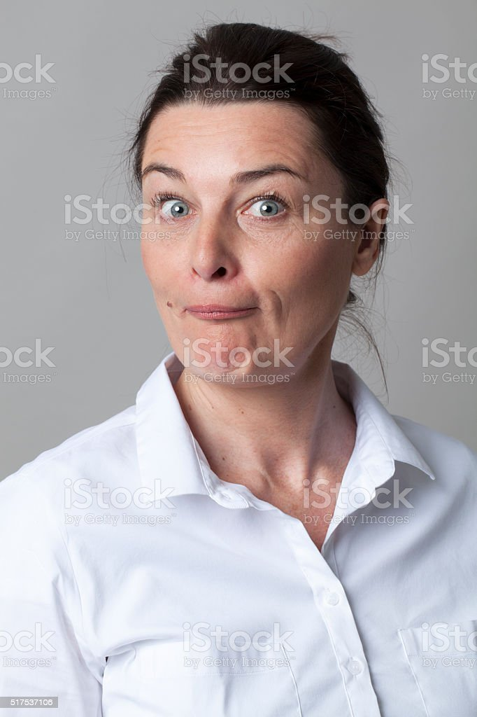 stunned smart middle aged woman with smart white shirt questioning stock photo