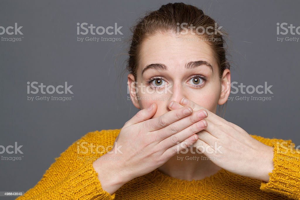 stunned young woman covering her mouth for mistake or regret stock photo