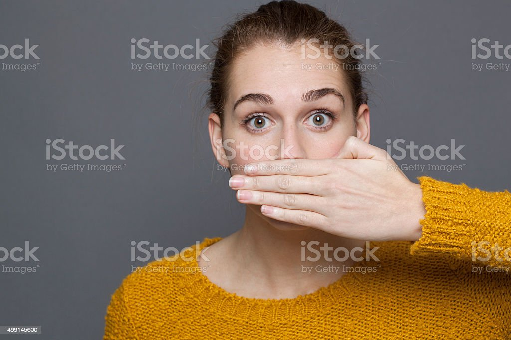 stunned young woman covering her mouth for silence stock photo