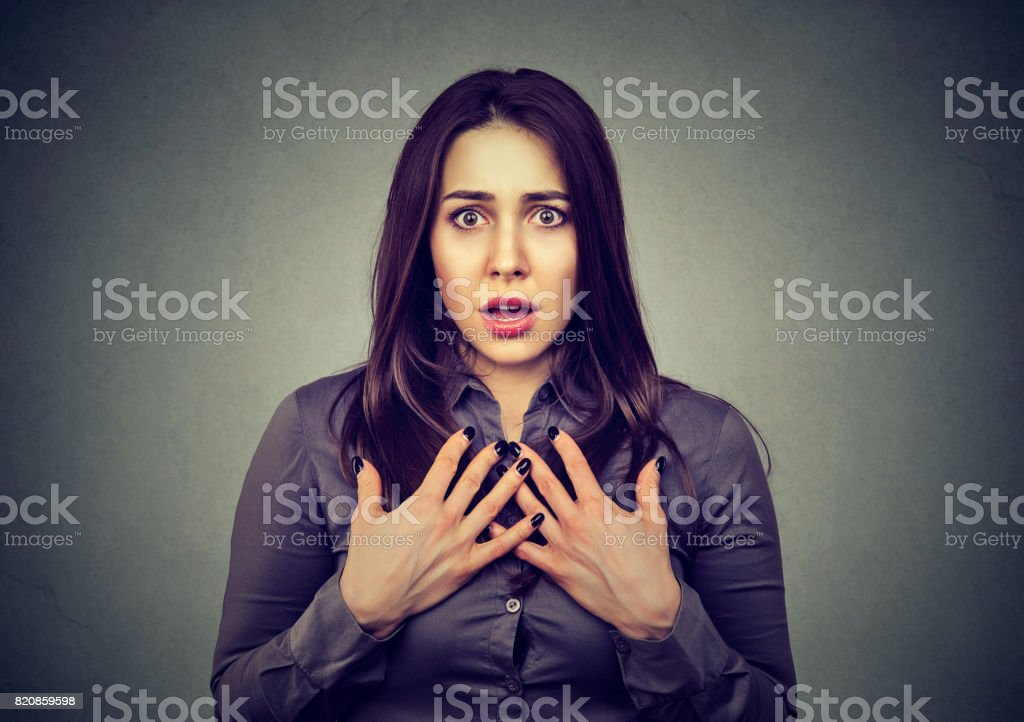 Stunned young woman looking at camera stock photo