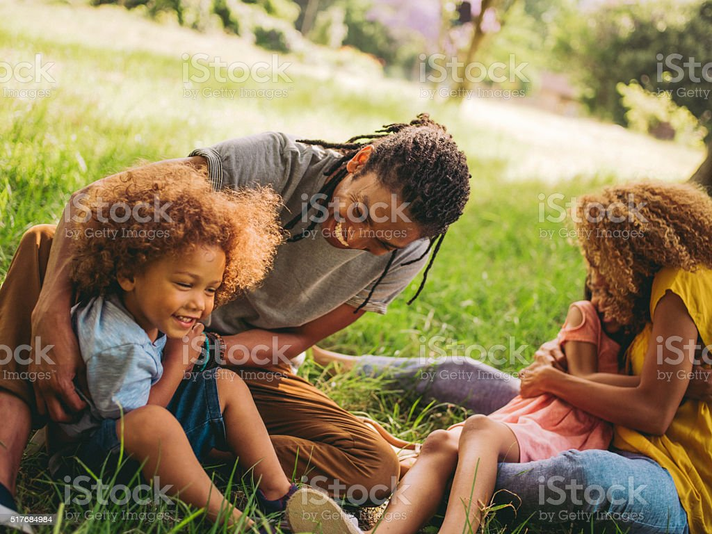 Stunning african-american family relaxing under a tree in park stock photo
