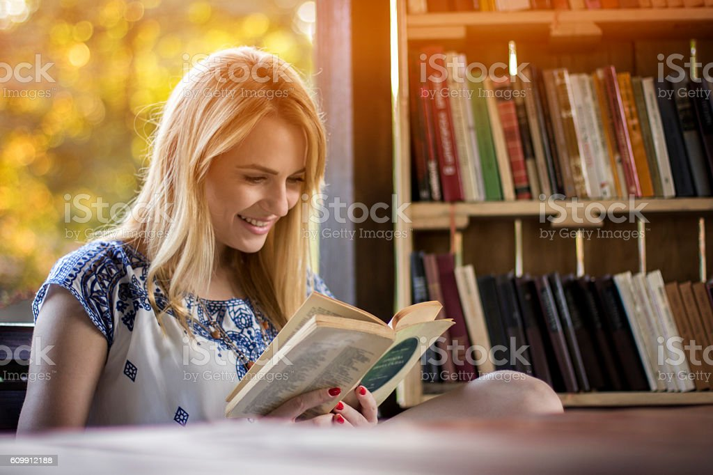 Stunning blonde reading book in nature stock photo