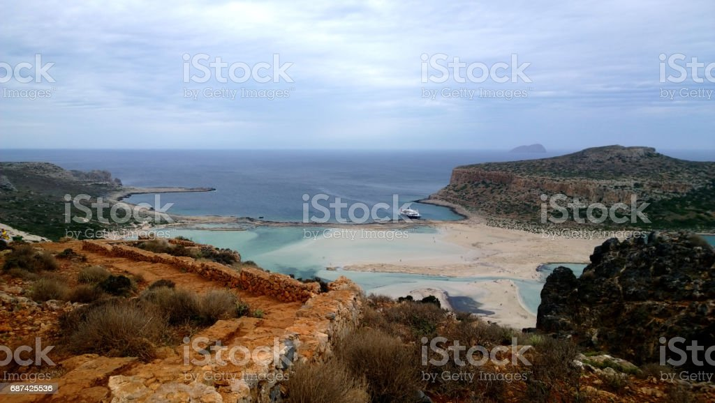 Stunning bright views of the famous Bay of Balos in Crete. Destroyed bright brown wall in foreground, the sea and the ship in the distance stock photo