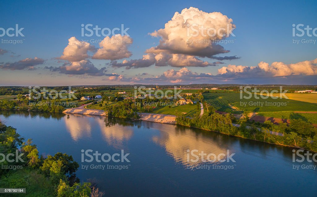 Stunning Cumulonimbus clouds reflected in calm river surface stock photo