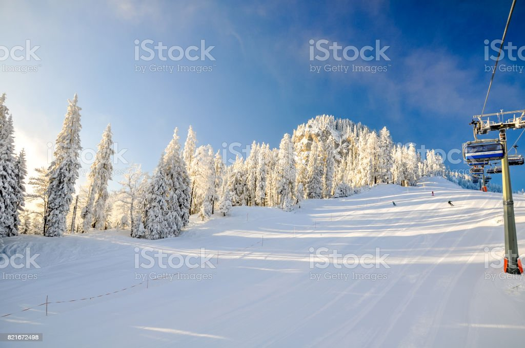 Stunning early morning shot of a ski slope and a chair lift near the Bavarian town of Garmisch Partenkirchen near Zugspitze mountain in Germany. Beautiful snow-covered trees in the background. stock photo