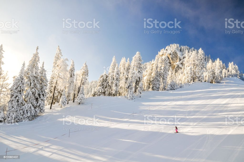 Stunning early morning shot of a ski slope with one skier near the Bavarian town of Garmisch Partenkirchen near Zugspitze mountain in Germany. Beautiful snow-covered trees in the background. stock photo