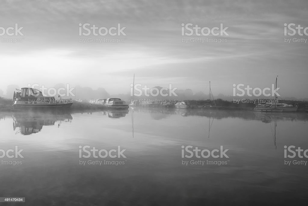 Stunning foggy Summer sunrise over peaceful river landscape in b stock photo