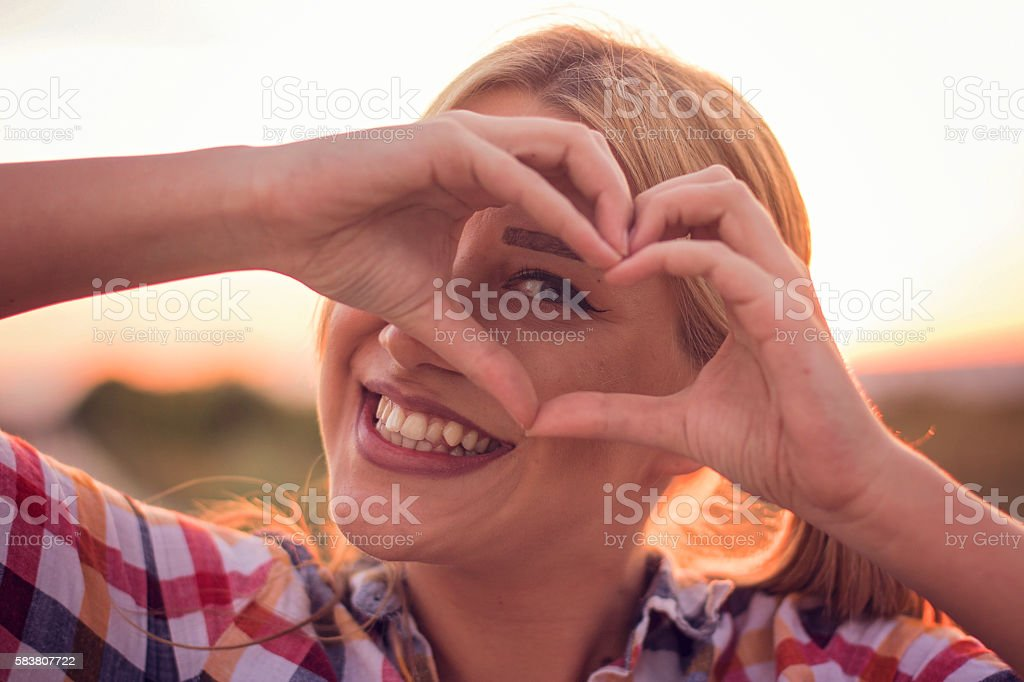 Stunning girl heart framing sun with hands stock photo